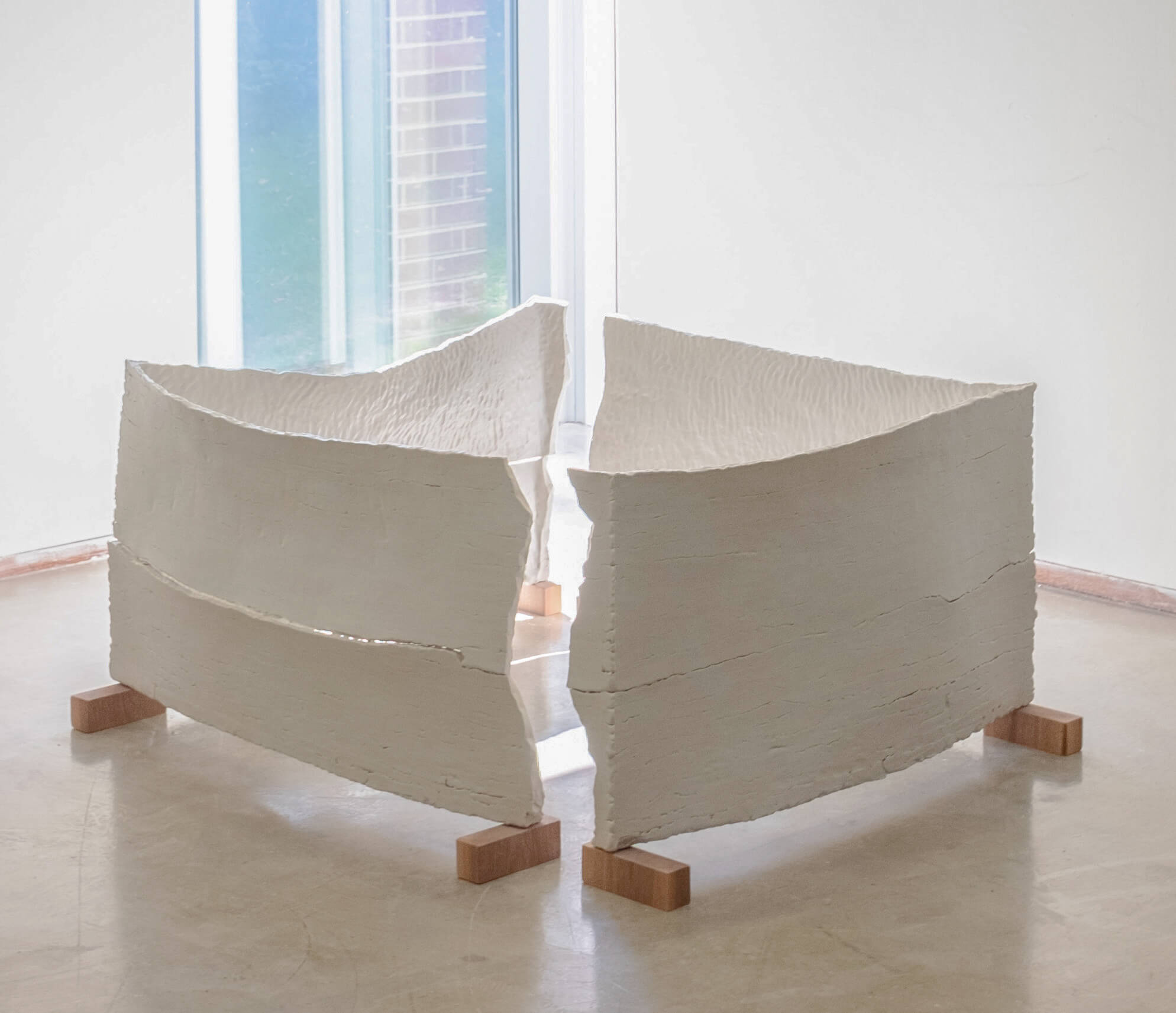 Large white square sculpture resting on concrete floor
