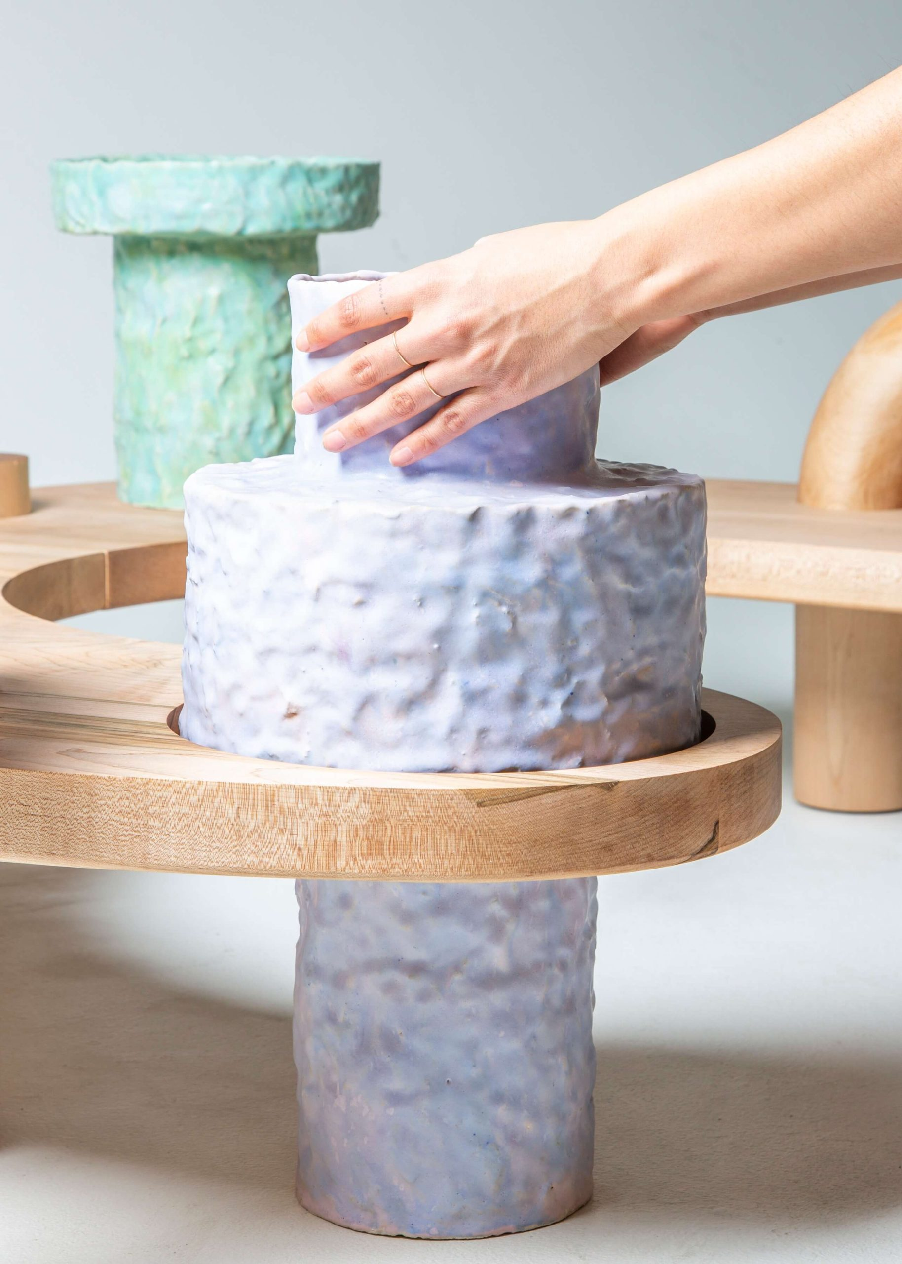 close up person touching large curved horizontal sculpture, light colored wood with pastel ceramic pots