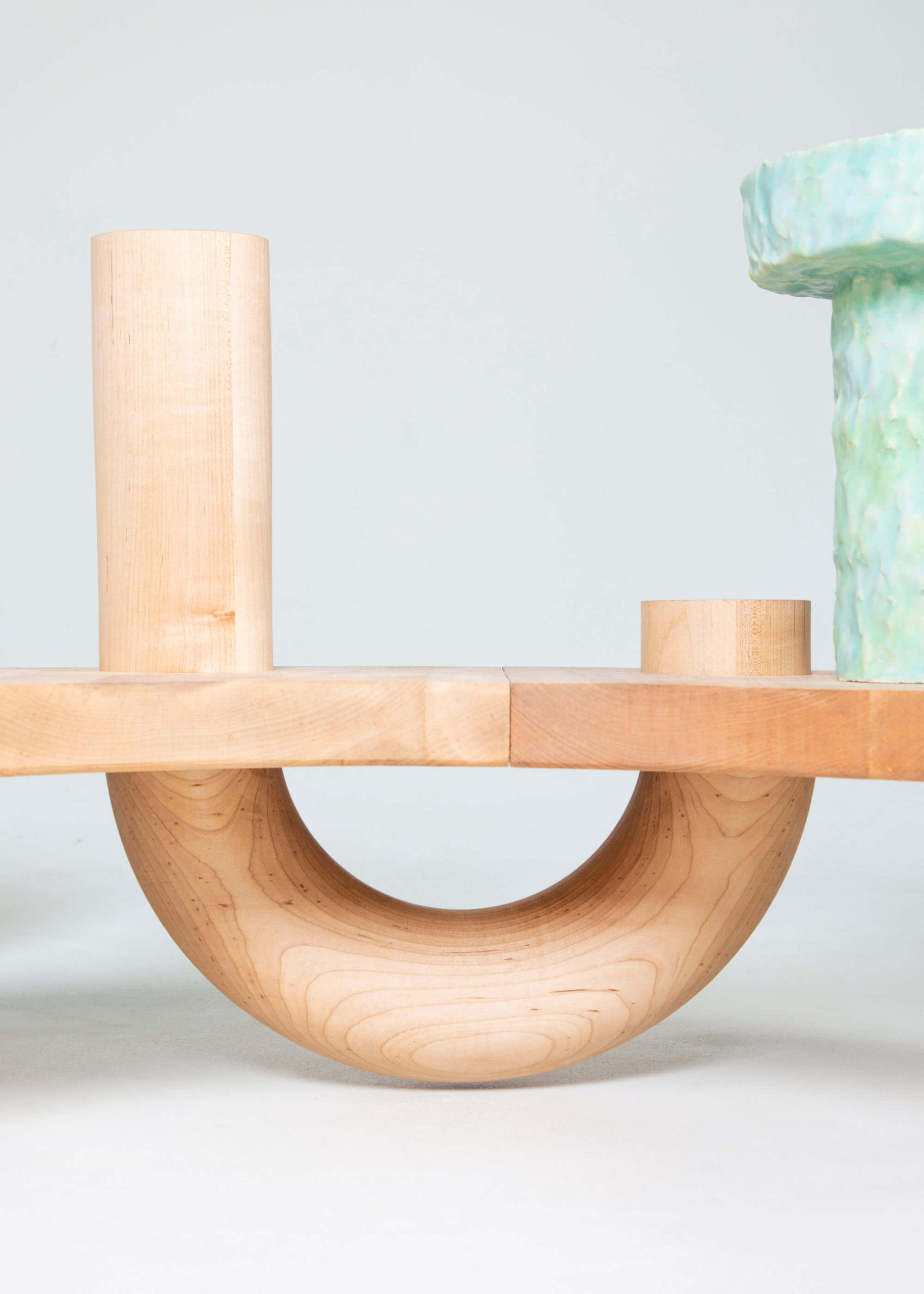 close up of large curved horizontal sculpture, light colored wood with pastel ceramic pots
