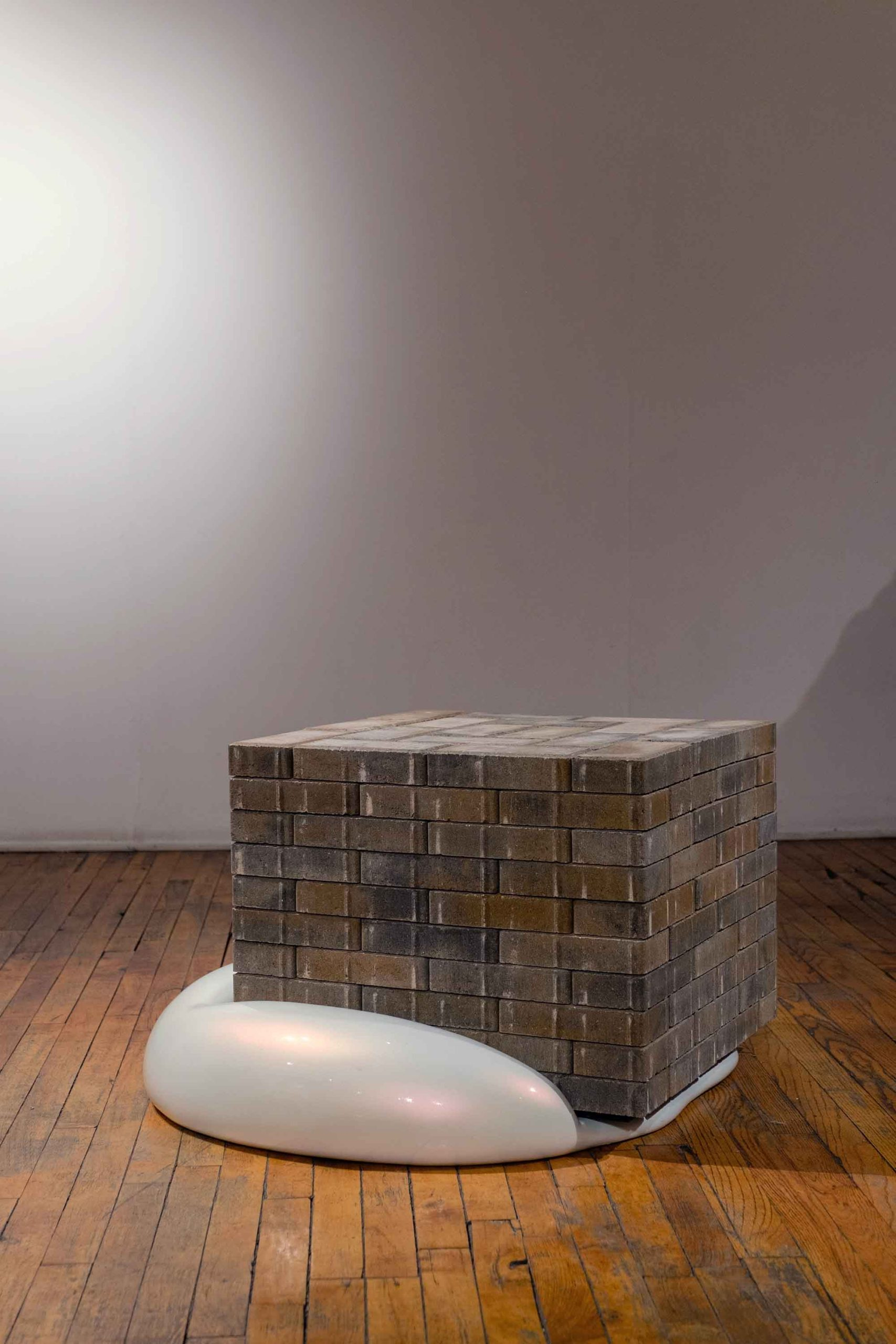 Round, organic sculpture, squashed by brick cube resting on wood floor