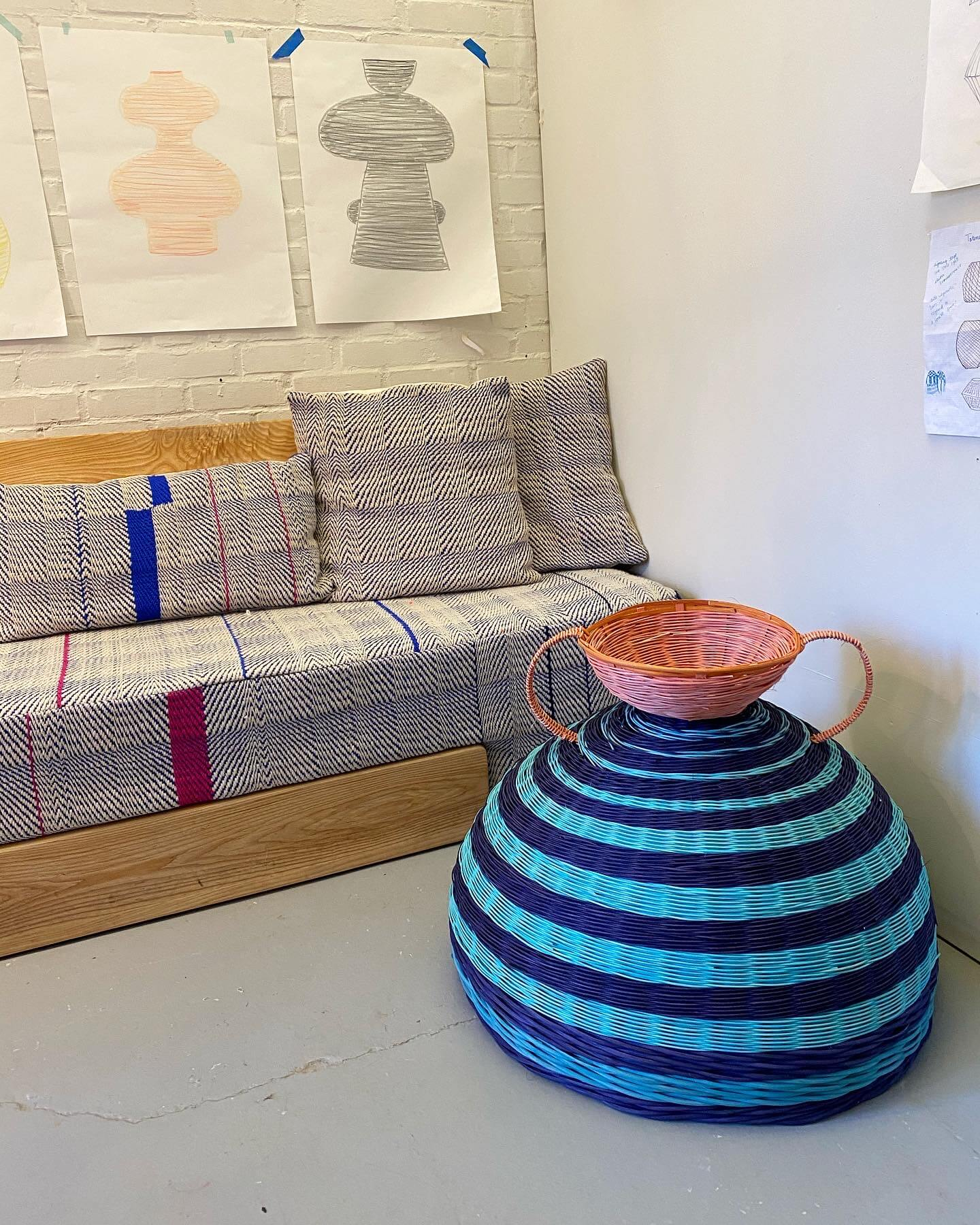 striped hand woven bowl and side table in front of sofa