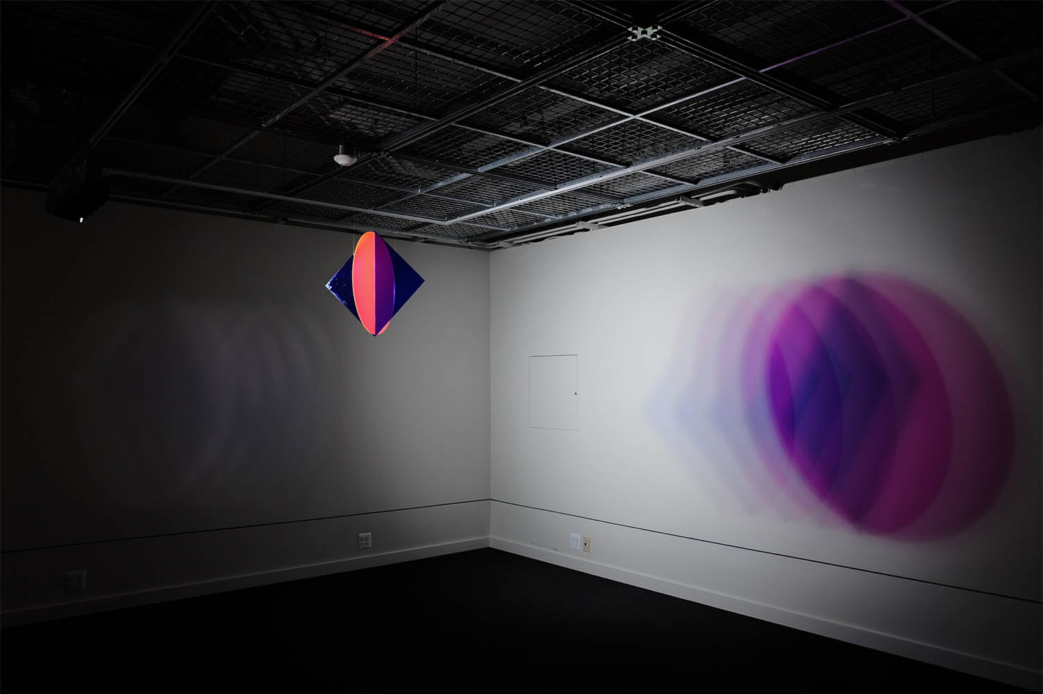 Circular suspended sculpture, reflecting purple light onto wall