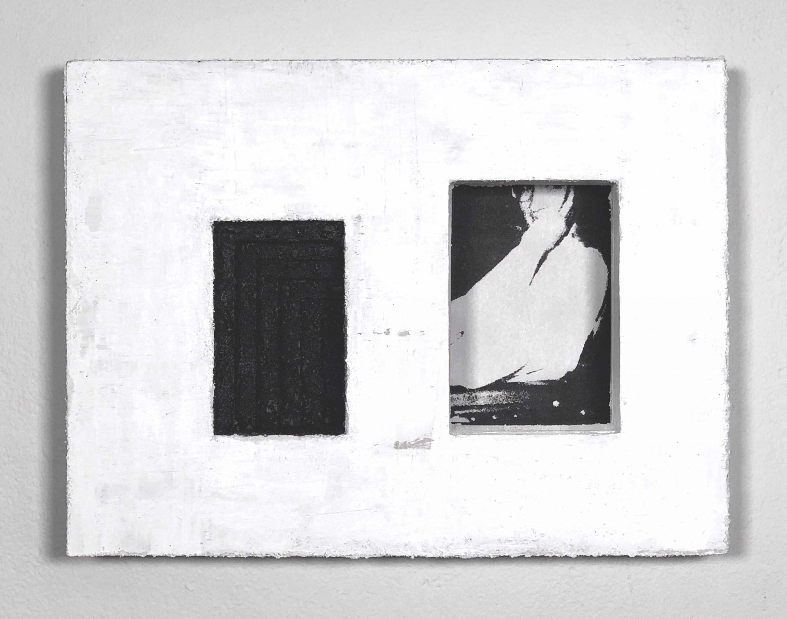 White rectangular block with two rectangular insets of different sizes. The left inset area is black with tonal geometric lines. The right inset area is slightly larger and holds a print. The print is a high-contrast, close up portrait of a person leaning on their arm with forearm and hand drawn up to their face.