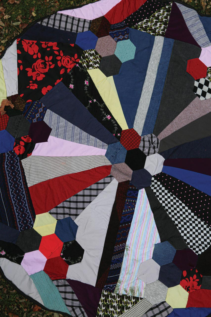 Overhead close up of a hand-made quilt. Various narrow triangles, hexagons, and other irregular shapes are created from multiple colors of different fabric.