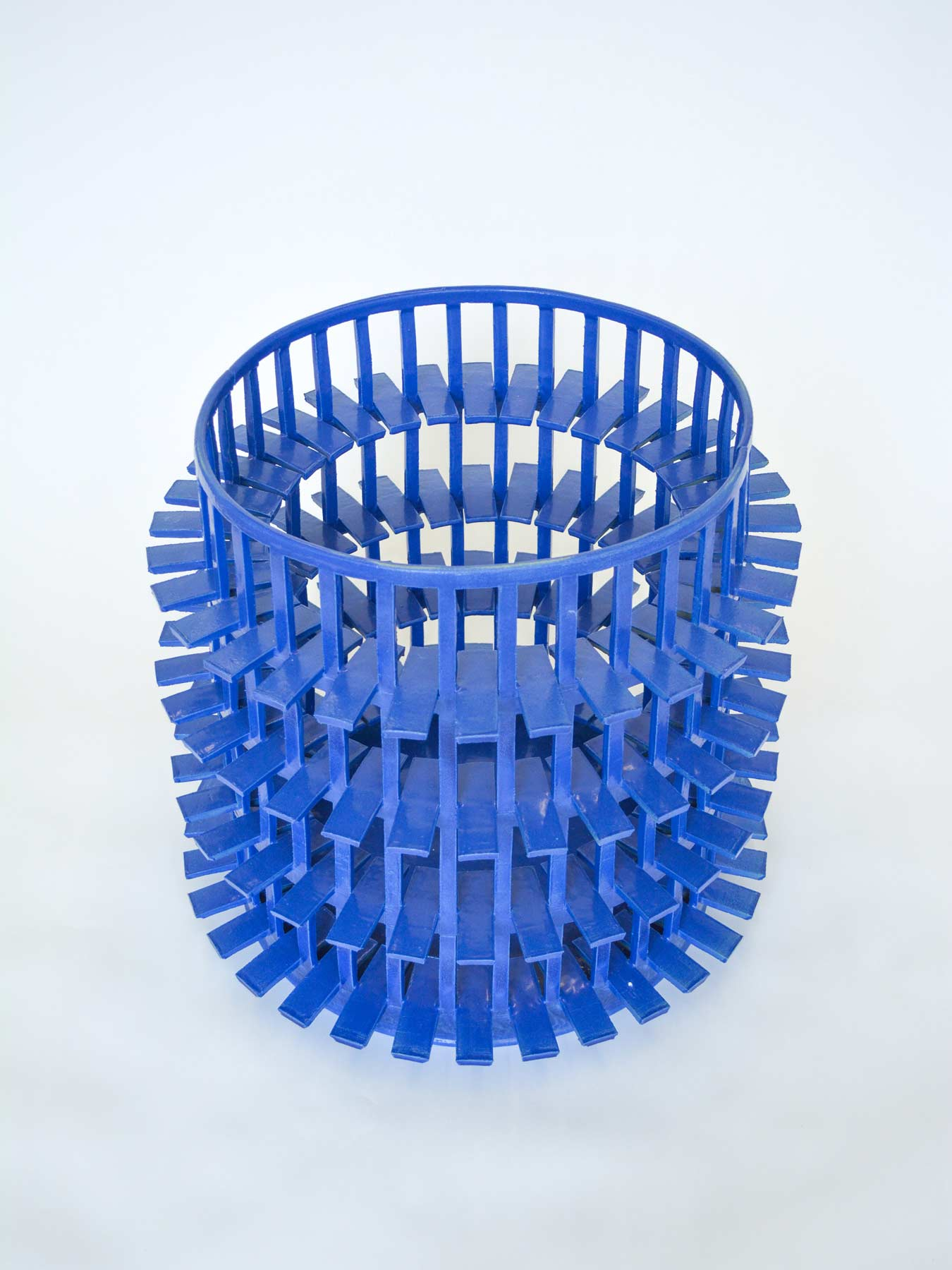 Large, wide blue stoneware vessel. Exterior is made up of a grid structure. Irregular white stones are inserted into the spaces formed by the grid.