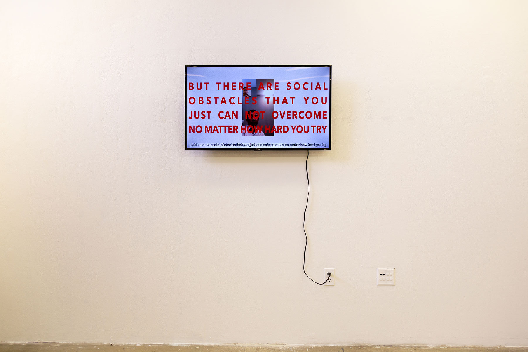 """A screen mounted on a white wall. Text on screen reads, """"But there are social obstacles that you just can not overcome no matter how hard you try"""" in all capital letters. The text is laid oer an image of two people speaking via video call on a smartphone."""