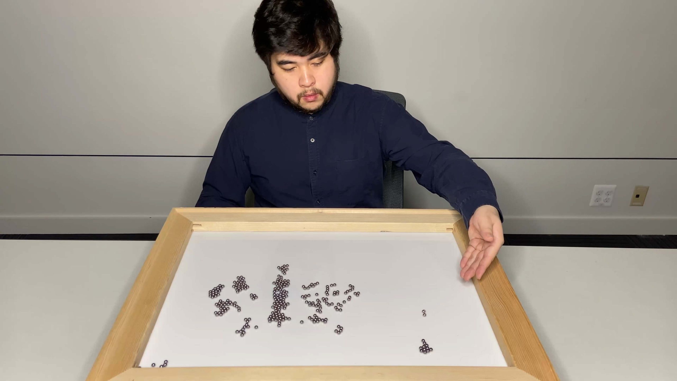 A person sitting down observing small moving objects in a light wood frame laid flat on the table.