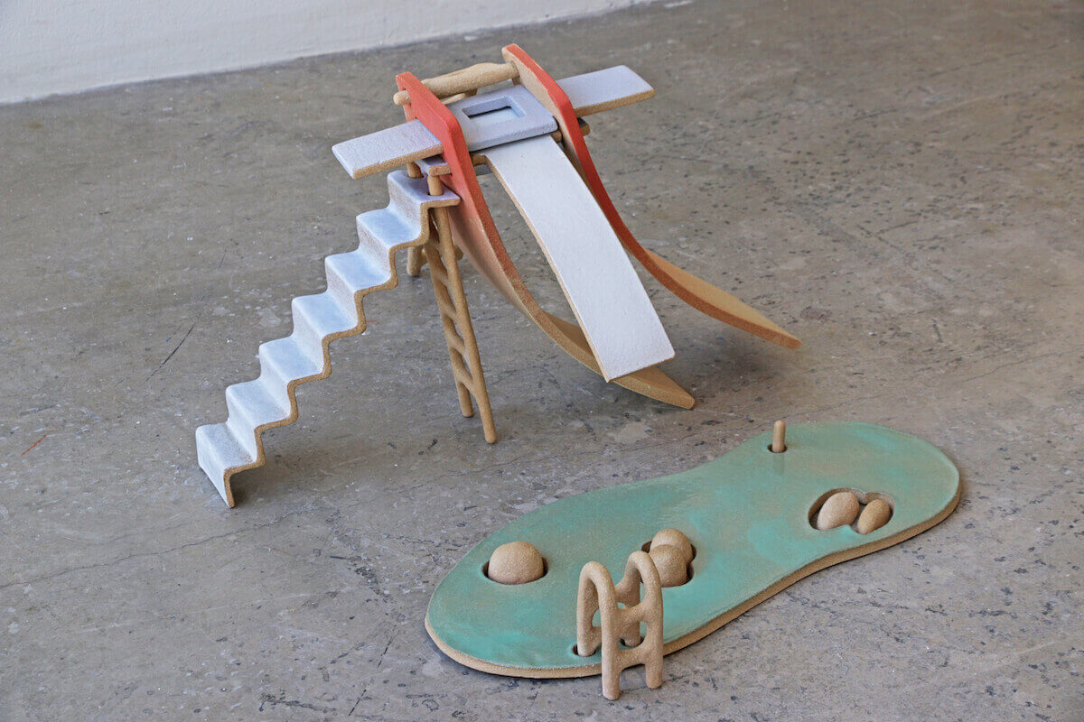 Two ceramics sculptures with muted colors depicting a diving board-like structure with stairway and an organic shaped green/blue surface with small round shapes breaking surface.