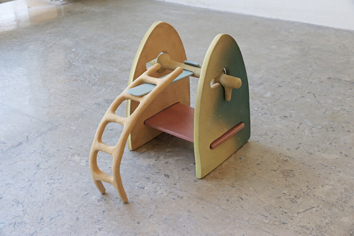 Multicolored ceramic sculpture depicting an arched playground ladder structure.