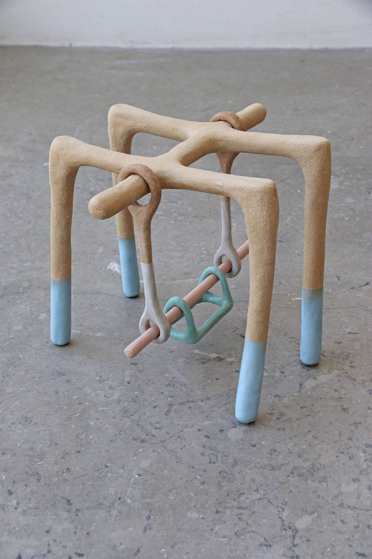 Ceramic sculpture in beige and light blue depicting rectangular bars supporting a simple bar swing.