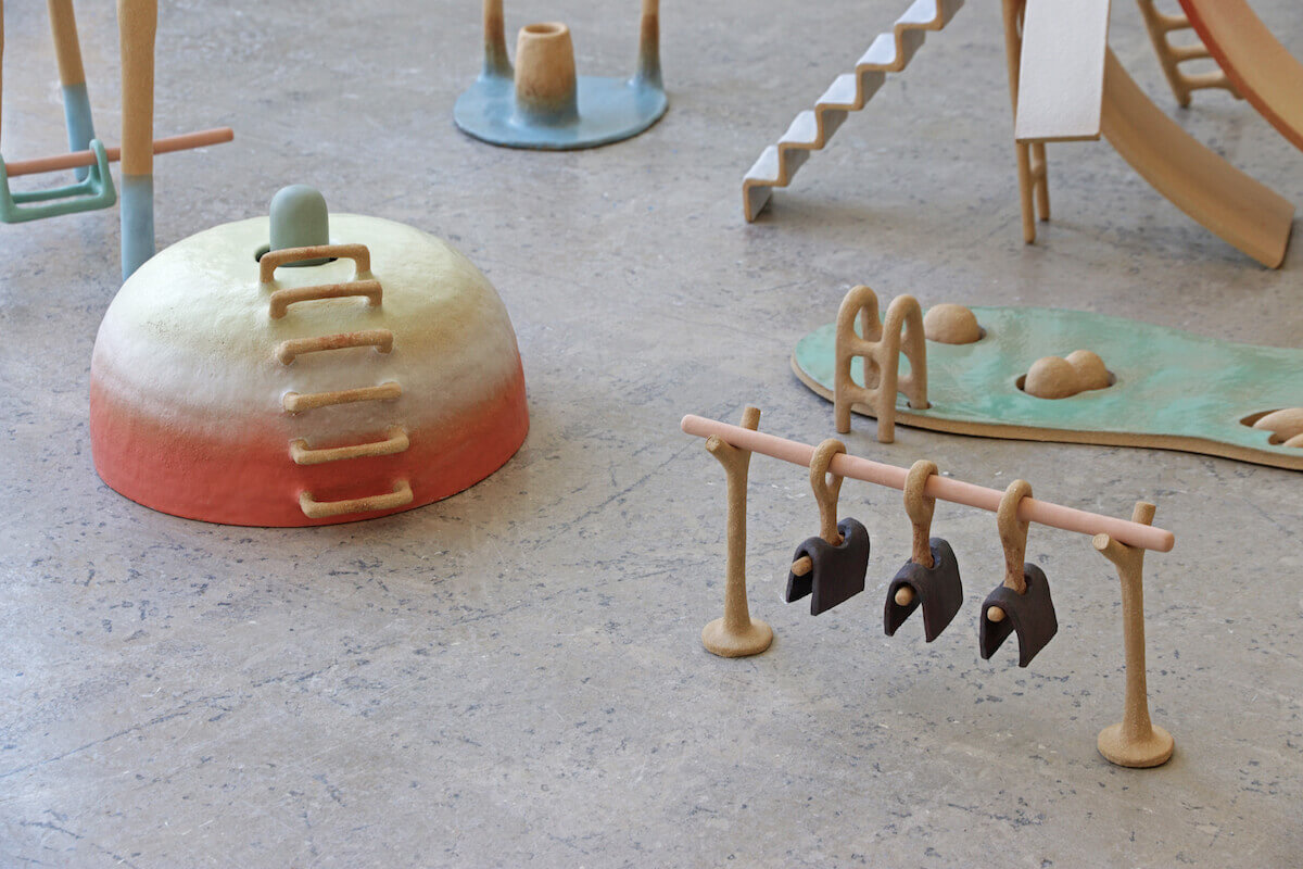 Two multicolored ceramic sculptures. Left is circular dome, reddish at bottom fading to cream at top. Small beige ladder rungs run from base to top. On the right, a beige rack holds three hangers holding folded purple shapes.