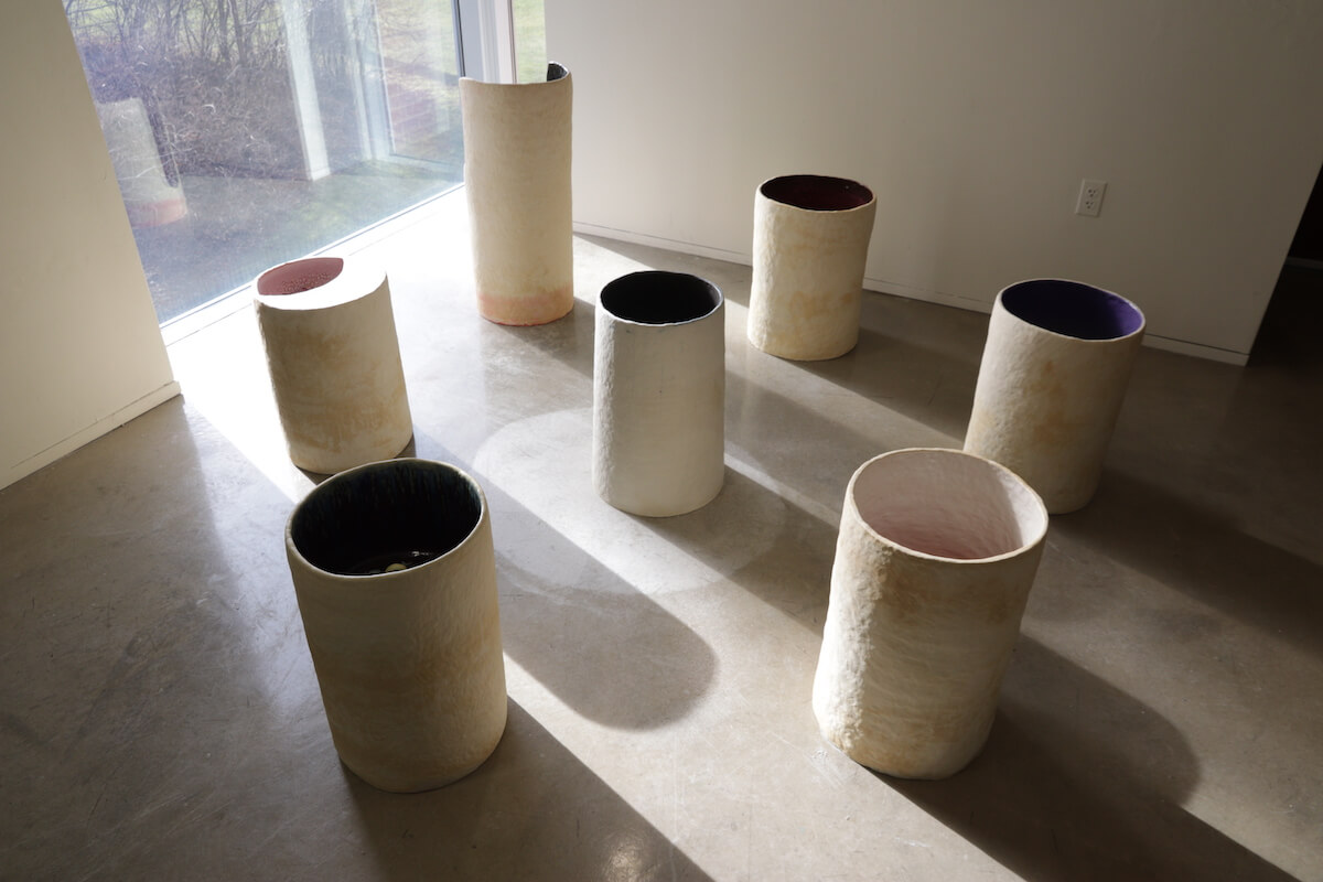 Grouping of large cream colored cylinders sitting on concrete floor in front of a window. Strong angled sunlight form long shadows of the cylinders.