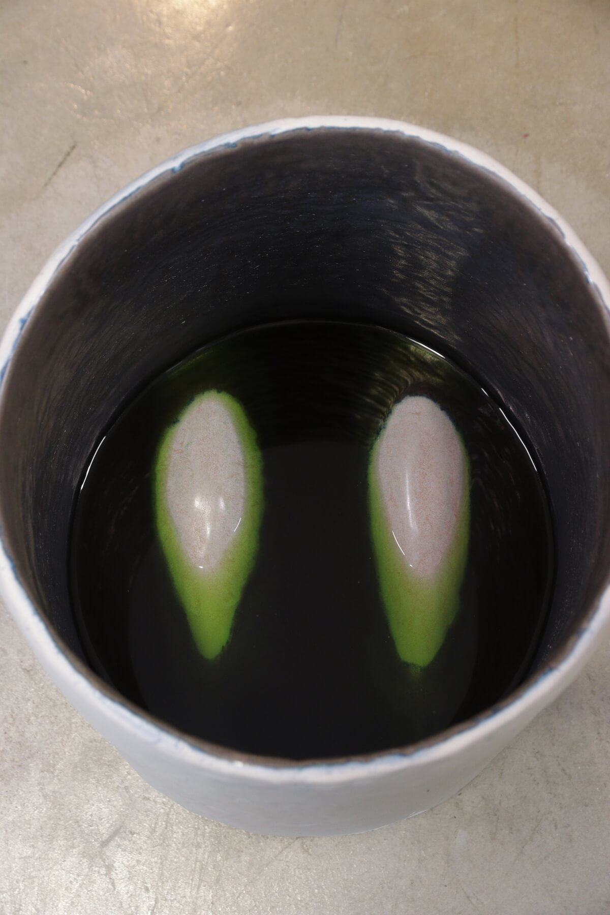 Interior of white/cream ceramic cylinder. Two rounded shapes poke out of green liquid-looking glaze.