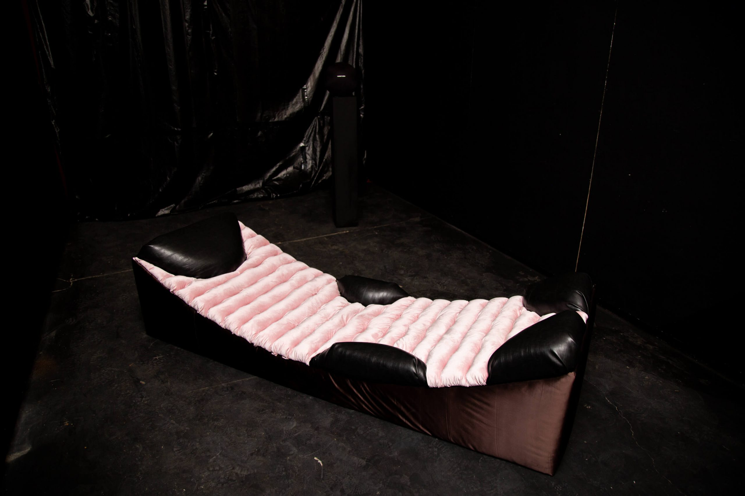 A pink and black low couch sits on black floor in front of black wall
