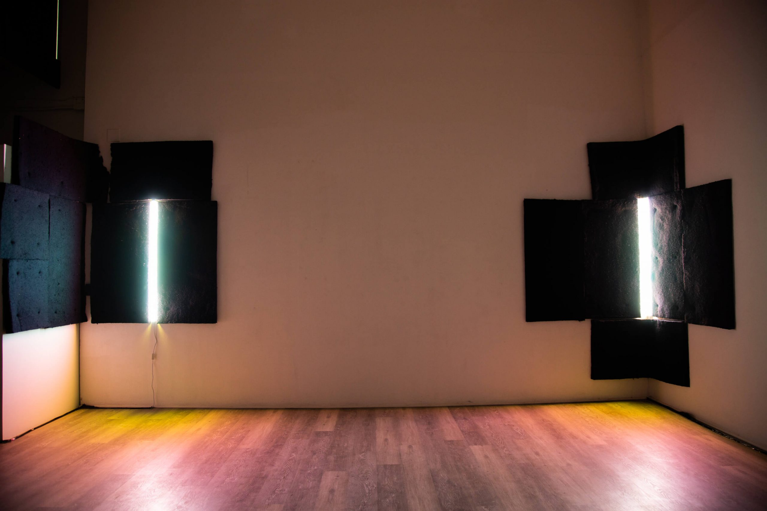 Two abstract lit sculptures hand in left and right corner of a room. Each sculpture in a vertical LED bar set into a geometric, rectangular shape that fits into the corner.