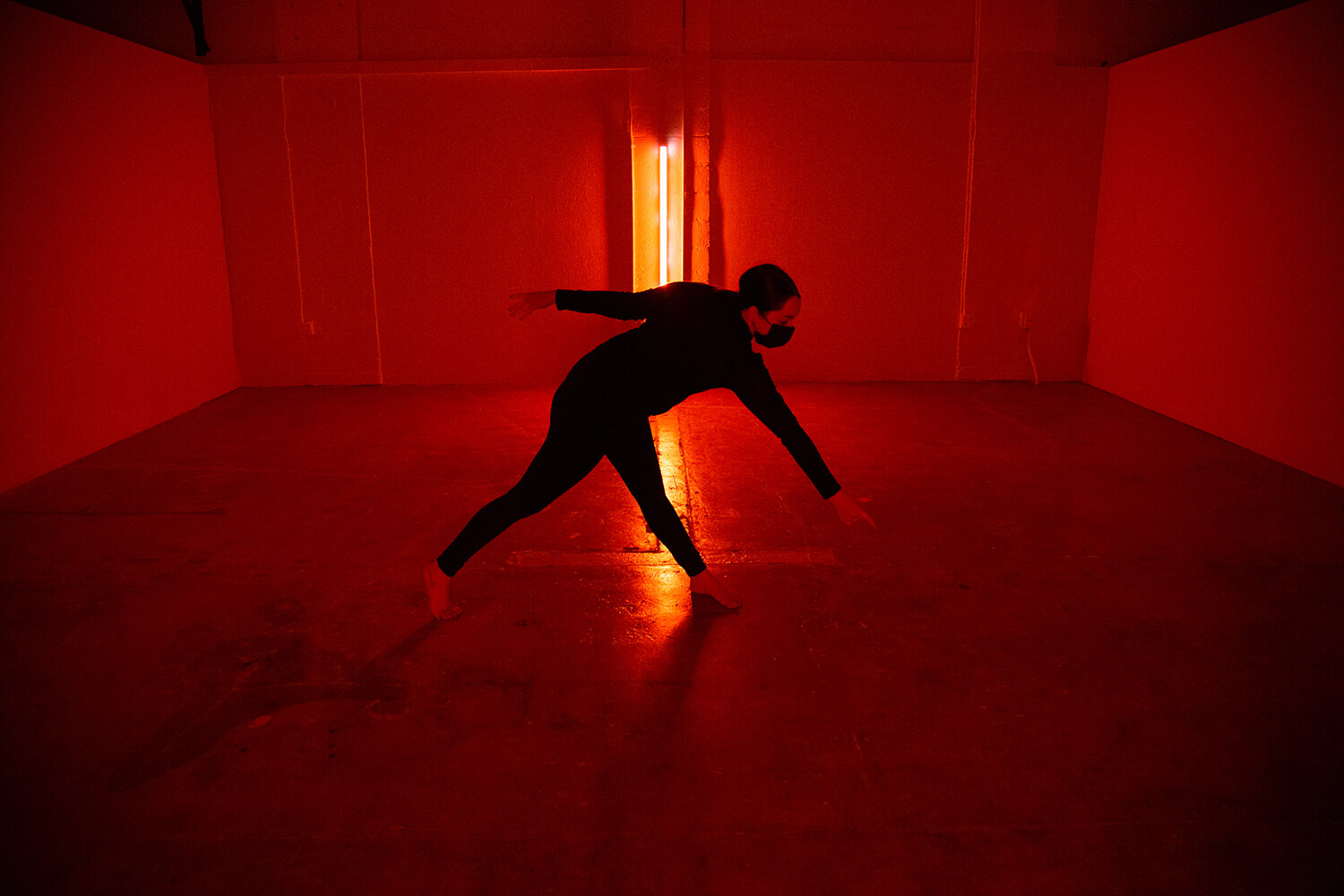 Person dressed in black with arms and legs outstretched in a red-lit room.