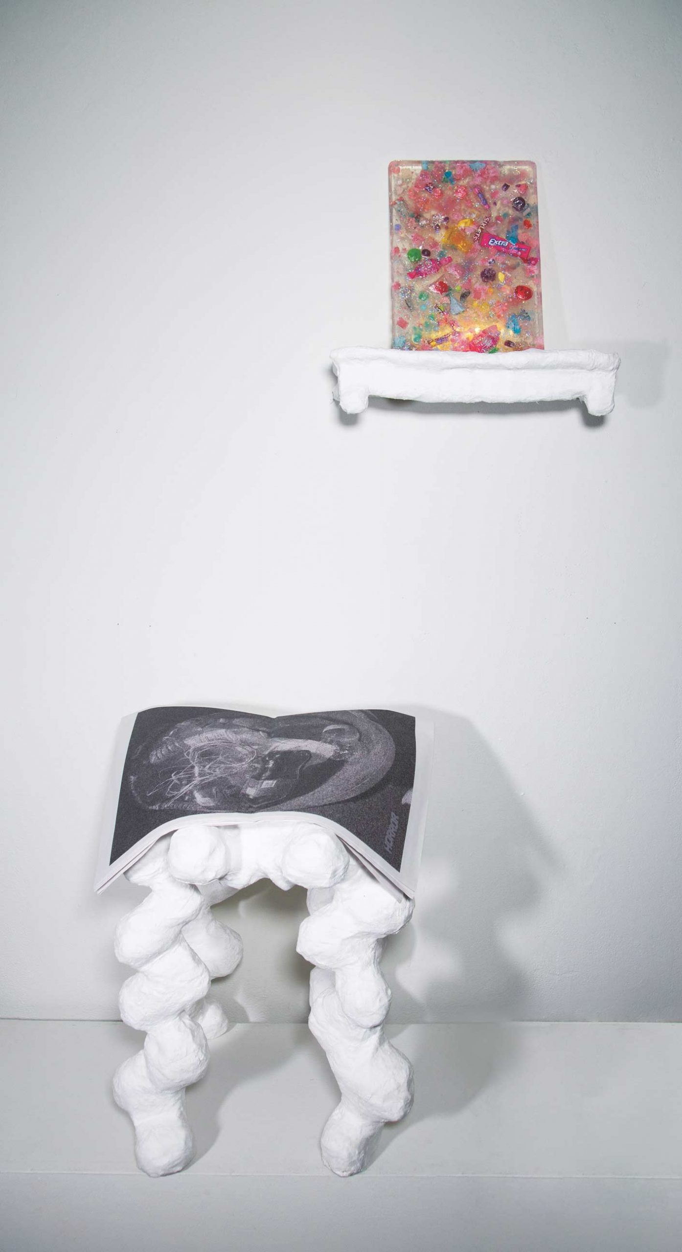 An installation featuring an organic-shaped, four-legged stool with an open black and white newspaper-like publication lying open and draped over the surface. The pages are open to a full page spread of a printed image. Above the stool and to the right is a white shelf with a colorful three-dimensional rectangle seated on it. The rectangle is a semi-transparent material with many colored objects embedded within.
