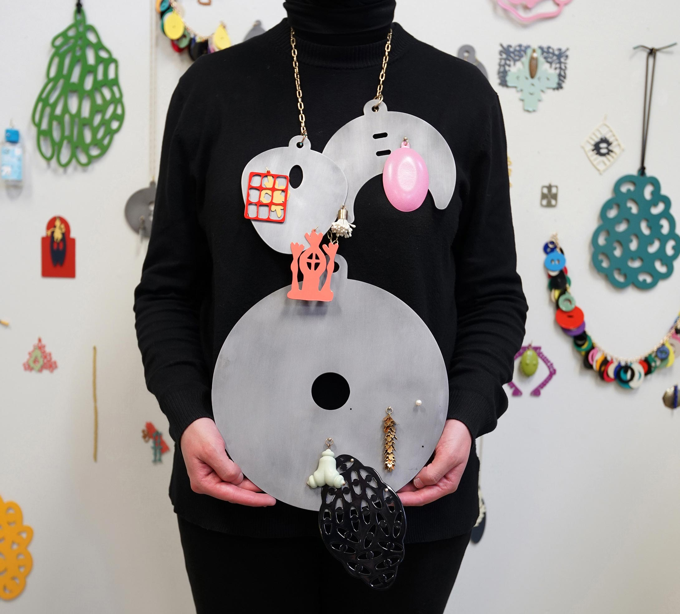 Close up on torso of person holding of a large metallic necklace made of metal discs and other shapes