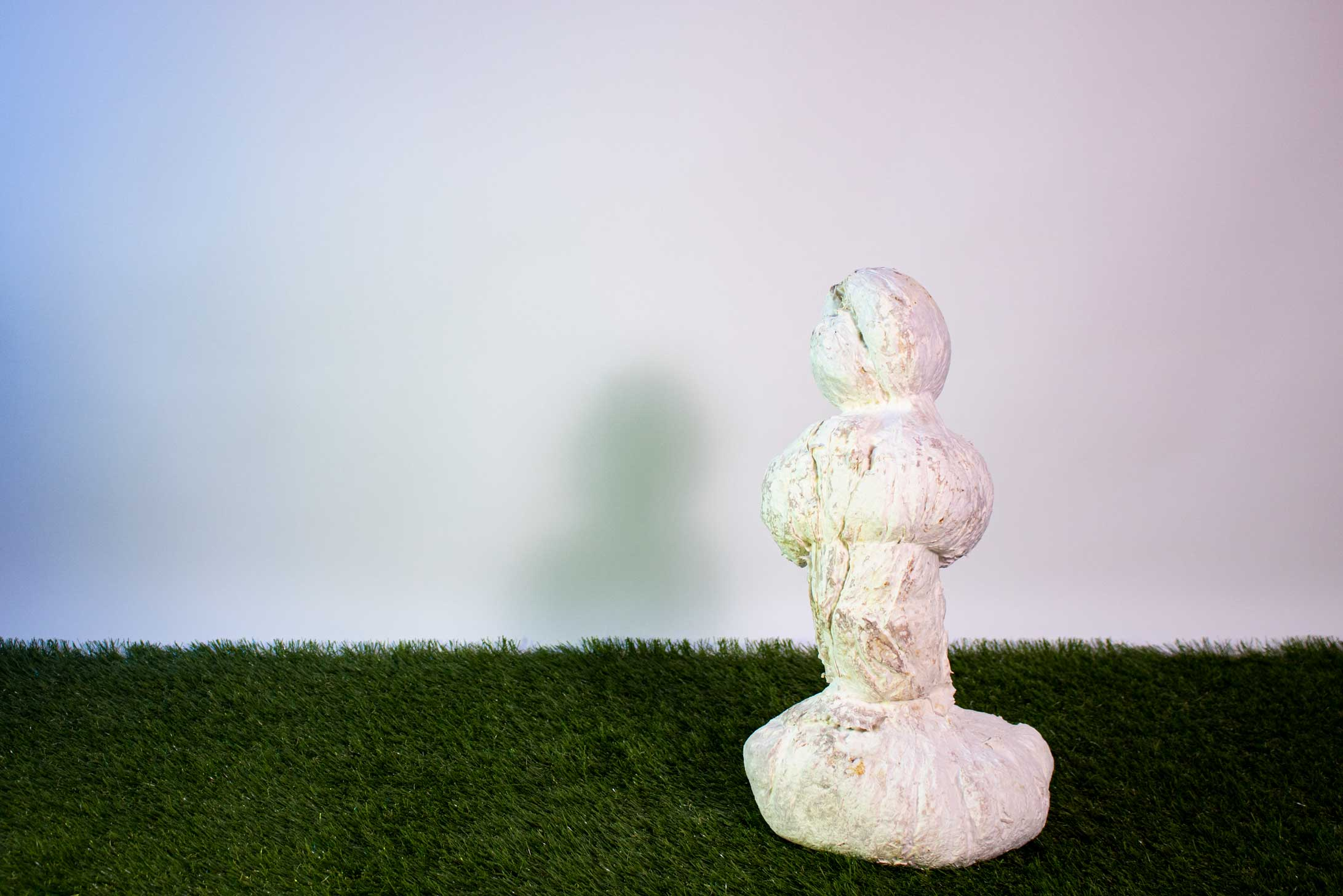A white/cream textured, organic sculpture sits on faux grass in front of a white wall.