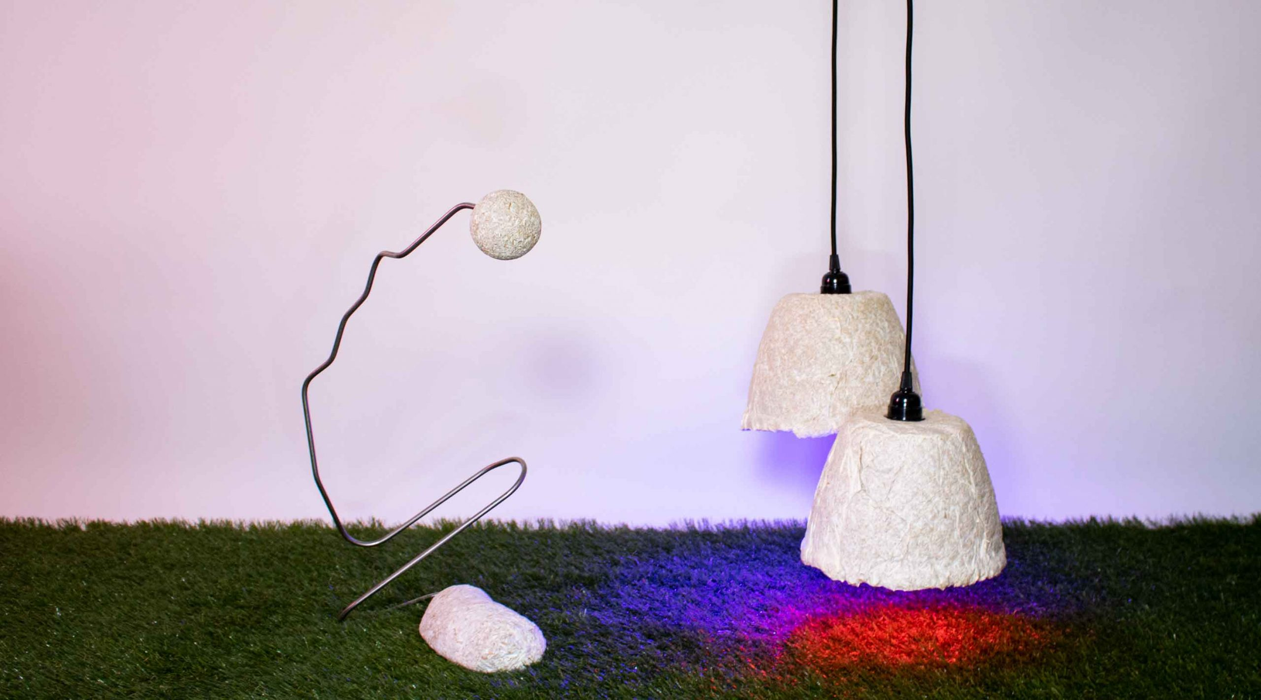 Several textured, organic sculptural objects sitting on faux grass in front of white wall. On the left, two white organic shapes balance on the bottom and top of a curved black wire. On the right, two white or cream organic lamp shades hang from black wires.