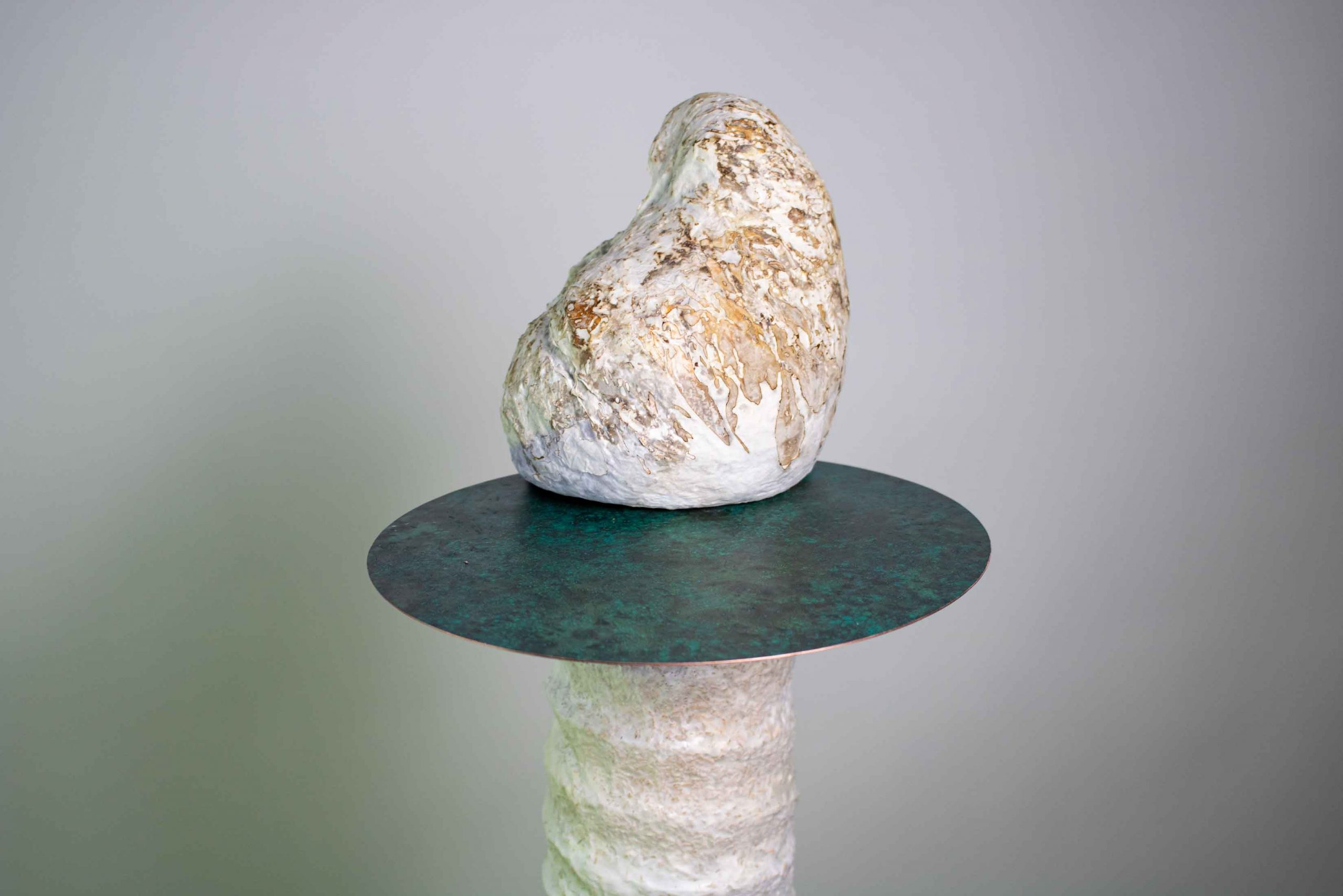 Detail of small white organic shaped sculptures balanced on a round copper plate sitting on top of a post-like structure.