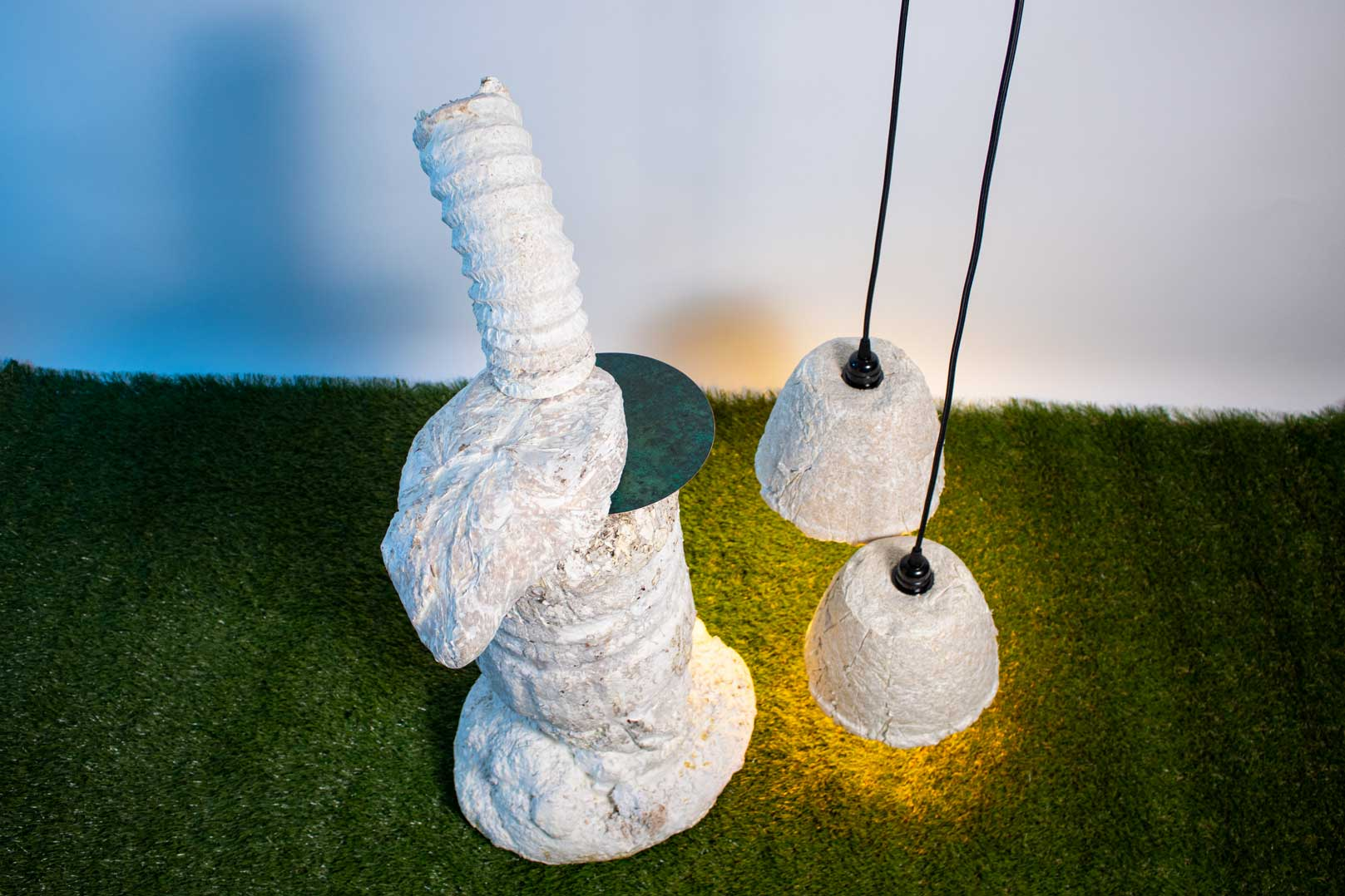Top down view of organic white/cream ceramic sculpture sitting on faux grass surface. To the right, two light colored organic ceramic lamps hang from black wiring. The lam ps cast a warm yellow glow over the faux grass and white wall.