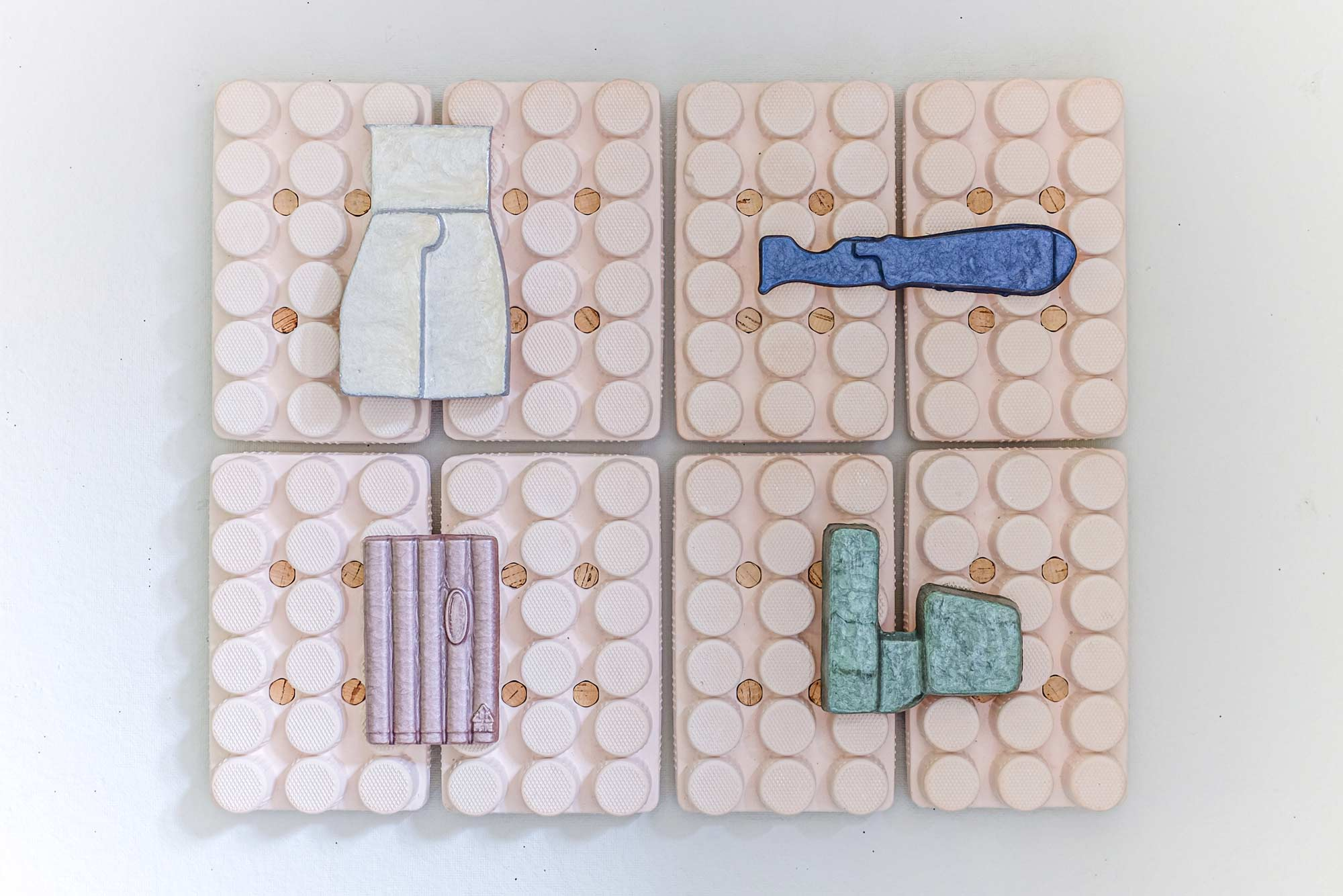 Four organic shapes in white, blue, pink, and green set into a surrounding rectangular pink sculpture with grid texture.