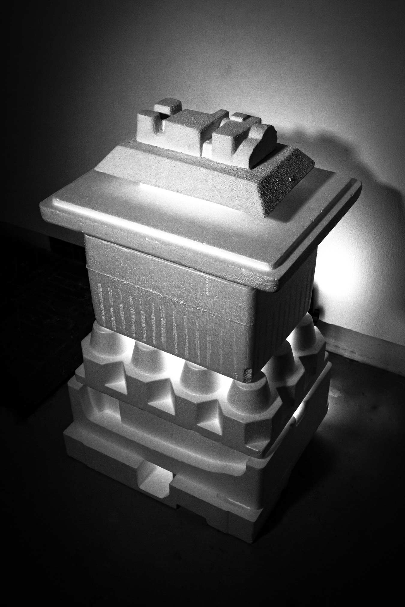 Dramatically lit black and white photo print of an architectural sculpture (angled view). Features a rectangular base, cone-like structures, then another rectangular section. On top is a flat-topped rectangular pyramid.